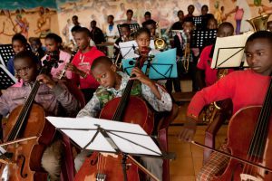 "Nairobi, Kenya. The ""Ghetto Classic"" orchestra, whose players are all students of the Korogocho school, during a concert rehearsal at St. John's parish in Korogocho slum. Every now and then, the orchestra plays for the public in these same premises."